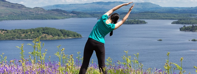 Woman yoga pose on a hill